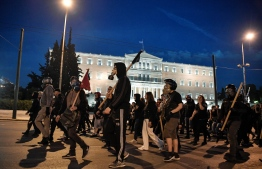 Anti-authoriterian protesters march in front of the Greek parliament in Athens on May 14, 2019 during a demonstration in support to hunger-striking far-left extremist serving 11 life terms for a string of murders, Dimitris Koufodinas, chief hit man for the November 17 group. - Koufodinas, 61, is in hospital due to the hunger strike he started May 2, after authorities in his prison  rejected again his furlough request. (Photo by LOUISA GOULIAMAKI / AFP)