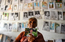A Sri Lankan Tamil woman holds a picture of a missing loved one at the Missing people organization office in the district of Mullaittivu on May 17, 2019, ahead of the 10th anniversary of Sri Lankan troops defeating Tamil Tiger rebels and declaring an end to a 37-year-old separatist war that claimed at least 100,000 lives. - Sri Lanka marks on May 18 and 19 a decade since the end of its 37-year Tamil separatist war that claimed at least 100,000 lives. (Photo by ISHARA S. KODIKARA / AFP)