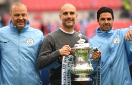Manchester City's Spanish manager Pep Guardiola (C) holds the winner's trophy as the team celebrates victory after the English FA Cup final football match between Manchester City and Watford at Wembley Stadium in London, on May 18, 2019. - Manchester City beat Watford 6-0 at Wembley to claim the FA Cup. (Photo by Daniel LEAL-OLIVAS / AFP) / NOT FOR MARKETING OR ADVERTISING USE / RESTRICTED TO EDITORIAL USE