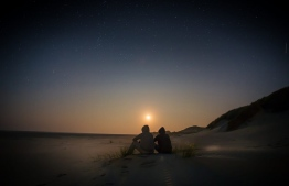 A couple watches the sun rise on a beach.