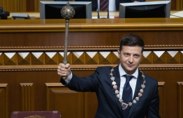 This picture taken and released by presidential press-service on May 20, 2019 shows Ukraine's President Volodymyr Zelensky holding the Bulava, the Ukrainian symbol of power, during his inauguration ceremony at the parliament in Kiev. (Photo by Markiv Mykhailo / UKRAINIAN PRESIDENTIAL PRESS SERVICE / AFP) /