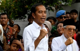Indonesian President Joko Widodo (C) and his running mate Ma'ruf Amin (R) gesture while visiting a neighbourhood in Jakarta on May 21, 2019. - Thousands of soldiers fanned out across Jakarta on May 21 after the surprise early announcement of official results in Indonesia's election showed Joko Widodo re-elected leader of the world's third-biggest democracy. (Photo by GOH Chai Hin / AFP)
