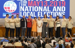 Philippines' Senators-elect, and allies of President Rodrigo Duterte, show the Duterte fist, (L-R) movie actor Bong Revilla, Francis Tolentino, movie actor Lito lapid, former national police chief Ronald dela Rosa, long-time advisor of Duterte, Christopher Bong Go, Cynthia Villar, Pia Cayetano, Sonny Angara, Imee Marcos, daughter of the late dictator Ferdinand Marcos, Aquilino Koko Pimentel III, while Independent candidates Grace Poe (6th R) and Nancy Binay (R) stand during the proclamation ceremony by the Commission on elections in Manila on May 22, 2019. - Allies of President Rodrigo Duterte stormed to a landslide victory in midterm polls, final results showed Masy 22, dissolving a last bulwark against his controversial rule. (Photo by Ted ALJIBE / AFP)