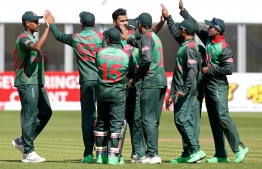 (FILES) In this file photo taken on May 13, 2019 Bangladesh's captain Mashrafe Mortaza (C) celebrates with teammates after taking the wicket of West Indies' Sunil Ambris (not pictured) during the Tri-Nation Series, one day international between Bangladesh and West Indies  Malahide cricket club, in Dublin on May 13, 2019. - Bangladesh have set their sights on capping a remarkable rise by reaching the World Cup semi-finals for the first time. Mashrafe Mortaza's team arrive in England confident of making the last four on the back of impressive form that marks them as a serious threat to the established order. (Photo by Paul Faith / AFP)