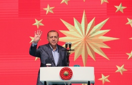 This handout picture released by the Turkish President's press office on May 12, 2019 shows Turkish President Recep Tayyip Erdogan flashes four fingers and makes the Rabia sign as he speaks during holy month of Ramadan, at Istiklal Avenue in Istanbul. (Photo by - / TURKISH PRESIDENTIAL PRESS SERVICE / AFP) /