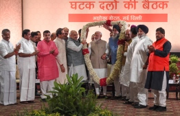Indian Prime Minister Narendra Modi (C) gestures as he is garlanded by Bharatiya Janata Party (BJP) and other alliance leaders during the National Democratic Alliance (NDA) dinner meeting in New Delhi on May 21, 2019. (Photo by Money SHARMA / AFP)
