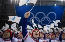 North Korean cheerleaders wave Unified Korea flags at the Pyeongchang Winter Olympics. PHOTO/AFP
