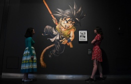 Museum employees pose next to an artwork of the manga series Dragon Ball, 1984-95 by Toriyama Akira during a press preview for the exhibition 'Manga' at the British Museum in central London on May 22, 2019. (Photo by Daniel LEAL-OLIVAS / AFP) /
