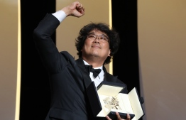 "South Korean director Bong Joon-Ho celebrates on stage with his trophy after he was awarded with the Palme d'Or for the film ""Parasite (Gisaengchung)"" on May 25, 2019 during the closing ceremony of the 72nd edition of the Cannes Film Festival in Cannes, southern France. (Photo by Valery HACHE / AFP)"