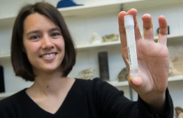 Assistant Professor Clara Blättler with a vial of seawater dating to the last Ice Age—about 20,000 years ago. PHOTO: Jean Lachat