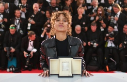 "French actress and film director Mati Diop poses during a photocall with her trophy after she won the Grand Prix for her film ""Atlantics (Atlantique)"" on May 25, 2019 during the closing ceremony of the 72nd edition of the Cannes Film Festival in Cannes, southern France. (Photo by Alberto PIZZOLI / AFP)"