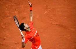 Serbia's Novak Djokovic serves the ball to Germany's Jan-Lennard Struff during their men's singles fourth round match on day nine of The Roland Garros 2019 French Open tennis tournament in Paris on June 3, 2019. (Photo by Martin BUREAU / AFP)