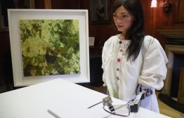 Robot artist 'Ai-Da' sketches using a pencil attached to her robotic arm, while standing next to a painting based on her computer vision data when run through algorithms developed by computer scientists in Oxford, Britain June 4, 2019. PHOTO: REUTERS/Matthew Stock