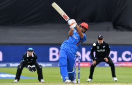 Afghanistan's Hazratullah Zazai plays a shot during the 2019 Cricket World Cup group stage match between Afghanistan and New Zealand at The County Ground in Taunton, southwest England, on June 8, 2019. - New Zealand's Colin de Grandhomme (R) drops a possible catch off Afghanistan's  Hazrat Zazai (Photo by Saeed KHAN / AFP) /