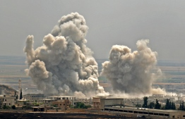 Plumes of smoke rise following reported Syrian government forces' bombardment on the town of Khan Sheikhun in the southern countryside of the jihadist-held Idlib province, on June 7, 2019. - Fierce clashes between government forces and jihadists have left 83 combatants dead in northwestern Syria in the past 24 hours, a Britain-based war monitor said on June 7. (Photo by Anas AL-dyab / AFP)