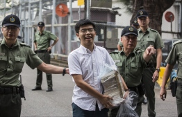 Hong Kong democracy activist Joshua Wong (C) leaves Lai Chi Kok Correctional Institute in Hong Kong on June 17, 2019. - Wong called on the city's pro-Beijing leader Carrie Lam to resign after he walked free from prison, as historic anti-government protests rocked the city. (Photo by ISAAC LAWRENCE / AFP)