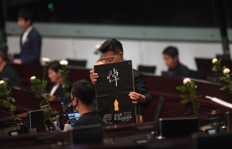 Pro-democracy lawmaker Gary Fan (C) holds a placard as he and other pro-democracy lawmakers hold five minutes of silence in the Legislative Council in Hong Kong on June 19, 2019, for a man who fell to his death on June 15 during a protest against a controversial extradition bill. - Massive rallies over the past two weeks against a Beijing-backed proposed law that would have allowed extraditions to mainland China have drawn support from a wide political and social spectrum, from students and activists to social workers and the business community, and -- based on figures from organisers -- were the biggest in Hong Kong's history. (Photo by Anthony WALLACE / AFP)