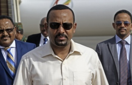 (FILES) In this file photo taken on June 07, 2019 Ethiopia's Prime Minister Abiy Ahmed (C) arrives at Khartoum international airport on June 7, 2019. - Ethiopia's Prime Minister Abiy Ahmed said on June 22, 2019 that the army chief of staff had been shot, however his condition was unknown after an evening of unrest in the Horn of Africa nation. (Photo by ASHRAF SHAZLY / AFP)
