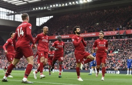 (FILES) A file photo taken on April 14, 2019 shows Liverpool's Egyptian midfielder Mohamed Salah (2nd-R) celebrating with teammates after scoring their second goal during the English Premier League football match between Liverpool and Chelsea at Anfield in Liverpool, north west England. - As a teenager, he spent ten hours travelling in Cairo to train for football. Today, at the age of 27, Mohamed Salah has won the Champions League and is one of the 100 most influential people in the world according to Time Magazine. (Photo by Paul ELLIS / AFP) / RESTRICTED TO EDITORIAL USE. No use with unauthorized audio, video, data, fixture lists, club/league logos or 'live' services. Online in-match use limited to 120 images. An additional 40 images may be used in extra time. No video emulation. Social media in-match use limited to 120 images. An additional 40 images may be used in extra time. No use in betting publications, games or single club/league/player publications. /