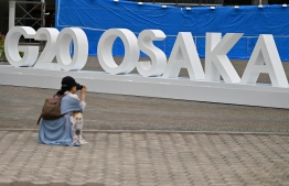 A woman takes a picture of a G20 Osaka design set up outside the venue for the G20 Osaka Summit in Osaka on June 26, 2019, ahead of the start of the summit later this week. (Photo by CHARLY TRIBALLEAU / AFP)