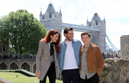 Actors Zendaya (L), Jake Gyllenhaal (C) and Tom Holland pose during a photocall for their latest film 'Spider-Man: Far From Home' at the Tower of London, backdropped by London's Tower Bridge, in London on June 17, 2019. (Photo by ISABEL INFANTES / AFP)