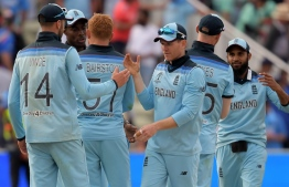 England's captain Eoin Morgan (C) celebrates with his players after victory in the 2019 Cricket World Cup group stage match between England and India at Edgbaston in Birmingham, central England, on June 30, 2019. (Photo by Dibyangshu Sarkar / AFP) /