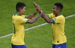 Brazil's Roberto Firmino (L) celebrates with Brazil's Gabriel Jesus after scoring against Argentina during their Copa America football tournament semi-final match at the Mineirao Stadium in Belo Horizonte, Brazil, on July 2, 2019. (Photo by MAURO PIMENTEL / AFP)