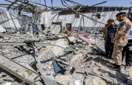 """Military officers of the Libyan Government of National Accord (GNA)inspect damage and debris at a migrant detention centre used by the GNA in the capital Tripoli's suburb of Tajoura on July 3, 2019, following an air strike on a nearby building that left dozens killed the previous night. - Over 40 migrants were killed in an air strike early late on July 2 on their detention centre in a Tripoli suburb blamed on Libyan strongman Khalifa Haftar, who has been trying for three months to seize the capital. The UN said the air strike """"may amount to a war crime"""". More than 130 people were also wounded in the in the raid on Tajoura, the statement added. (Photo by Mahmud TURKIA / AFP)"""