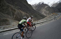 In this picture taken on June 30, 2019, Pakistani cyclists Najeeb Ullah (R) and Hanzala (L) compete during the Tour de Khunjerab, one of the world's highest altitude cycling competitions, at the Pakistan-China Khunjerab border. - Finishing nearly 5,000 metres above sea level after hundreds of kilometres winding past blackened glaciers and snow-capped peaks: a new Pakistani race presents a world-class challenge for cyclists -- climbing towards the 'Roof of the World'. (Photo by AAMIR QURESHI / AFP) /
