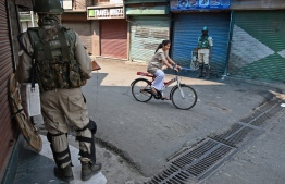 Indian paramilitary troopers stand guard as a Kashmiri girl rides a bicycle after authorities imposed restrictions on movement in Srinagar on July 8, 2019. - Indian authorities imposed restrictions of movement around the Jamia Masjid mosque in Srinagar on July 8 during a one-day strike called by Kashmiri seperatists on the third anniversary of the death of militant commander Burhan Wani. (Photo by STR / AFP)