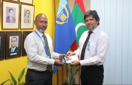 Commissioner General of Customs Ahmed Noomaan presents the letter of appointment and badge to the new Deputy Commissioners Abdulla Shareef. PHOTO: MALDIVES CUSTOMS