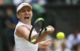 Romania's Simona Halep returns against Ukraine's Elina Svitolina during their women's singles semi-final match on day ten of the 2019 Wimbledon Championships at The All England Lawn Tennis Club in Wimbledon, southwest London, on July 11, 2019. (Photo by Daniel LEAL-OLIVAS / AFP) /