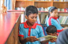A student choosing a book in the newly opened Maaenboodhoo School library. PHOTO: BML
