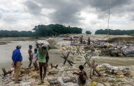 Locals gather concrete fragments and heavy bags wrapped in nets to build a dam as floodwaters flow from the north into the state of Indian eastern state of Bihar near Muzaffarpur on July 13, 2019. - Floods and landslides triggered by torrential monsoon rains have killed at least 40 people across South Asia in the last two days, officials said on July 13. (Photo by STR / AFP)