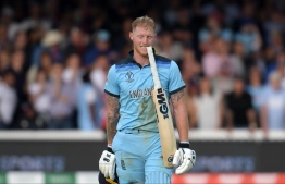 England's Ben Stokes holds his bat in his teeth ahead of a 'super over' during the 2019 Cricket World Cup final between England and New Zealand at Lord's Cricket Ground in London on July 14, 2019. (Photo by Dibyangshu Sarkar / AFP) /