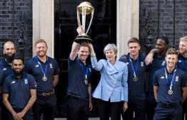 (L-R) England's Moeen Ali, England's Adil Rashid, England's Jonny Bairstow, England's captain Eoin Morgan, Britain's Prime Minister Theresa May, England's Jason Roy, England's Jofra Archer, England's Joe Root and England's Ben Stokes pose for a photograph outside 10 Downing Street with the World Cup trophy as England players arrive for a reception in London on July 15, 2019, a day after they won the 2019 Cricket World Cup after beating New Zealand the final at Lord's. (Photo by Niklas HALLE'N / AFP)