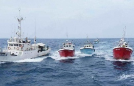 Foreign fishing boats and a vessel of the Maldives National Defence Force. PHOTO: MIHAARU