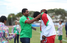 Minister of Sports Ahmed Mahloof giving the Bronze medal to Maazin for 100m Paralympic event. PHOTO: MOC / MOHAMED SHARUAAN WAHEED