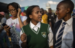 "(L to R) Keabetswe Lebakeng (15), Jennifer Ngobeni (16) and Michelle Selemela (17), members of ""Bigger than Life"" the Children's Radio Foundation team based in Alexandra walk through the streets on March 14, 2019 in Alexandra, Johannesburg. (Photo by GULSHAN KHAN / AFP)"