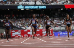 Jamaica's Shelly-Ann Fraser-Pryce (C) crosses the line ahead of second-placed Britain's Dina Asher-Smith (2L) and third-placed Ivory Coast's Marie-Josée Ta Lou (2R) in the Women's 100m Final event during the the IAAF Diamond League Anniversary Games athletics meeting at the London Stadium in London on July 21, 2019.  PHOTO: ADRIAN DENNIS / AFP