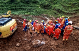 This photo taken on July 24, 2019 shows rescuers working at the site of a landslide in Liupanshui in China's southwestern Guizhou province. - The death toll in a landslide that buried a village in southwest China rose to 20 on July 26, with 25 people still missing three days after the disaster, state media said. (Photo by STR / AFP) /