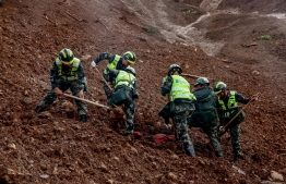 This photo taken on July 25, 2019 shows rescuers searching for survivors at the site of a landslide in Liupanshui in China's southwestern Guizhou province. - The death toll in a landslide that buried a village in southwest China rose to 20 on July 26, with 25 people still missing three days after the disaster, state media said. (Photo by STR / AFP) /