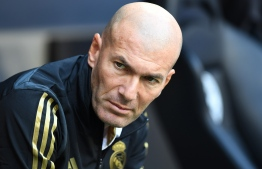 Real Madrid's French coach Zinedine Zidane waits ahead the Audi Cup football match between Real Madrid and Tottenham Hotspur in Munich, on July 30, 2019. (Photo by Christof STACHE / AFP)