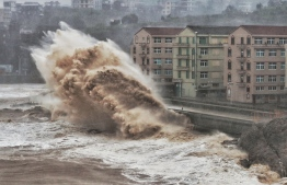 Waves hit a sea wall in front of buildings in Taizhou, China's eastern Zhejiang province on August 9, 2019. - China issued a red alert for incoming Super Typhoon Lekima which is expected to batter eastern Zhejiang province early on August 10 with high winds and torrential rainfall. (Photo by - / AFP) /