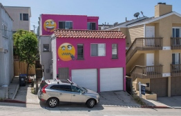 "View of the pink emoji house that has become embroiled in a feud between neighbors in Manhatten Beach, California on August 9, 2019. A house painted bright pink and adorned with two giant ""emoji"" faces is the latest salvo in a bitter feud between neighbors of a wealthy Los Angeles beach town. In a bid to preserve its distinctive ""small-town feel,"" Manhattan Beach banned short-term rentals lasting fewer than 30 days a few years ago. PHOTO: MARK RALSTON / AFP"