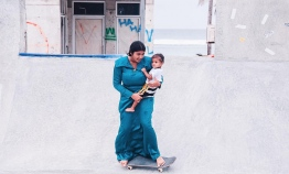 A mother skateboarding in traditional 'Dhigu Hedhun' while holding her son, wearing 'Feyli' and a white shirt. PHOTO: IYAD IBRAHIM