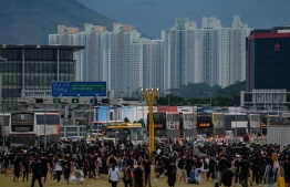 Protesters walk on a highway near Hong Kong's international airport following a protest against the police brutality and the controversial extradition bill on August 12, 2019. - Hong Kong airport authorities cancelled all remaining departing and arriving flights at the major travel hub on August 12, after thousands of protesters entered the arrivals hall to stage a demonstration. (Photo by Philip FONG / AFP)