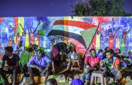 "(FILES) In this file photo taken on April 24, 2019, Sudanese protesters sit in front of a recently painted mural during a demonstration near the army headquarters in the capital Khartoum. - The graffiti that symbolised Sudan's uprising are being painted over across the capital Khartoum, protest leaders complained Wednesday, urging the military authorities to stop their whitewashing. The Forces for Freedom and Change that led the months-long protest movement that brought down longtime ruler Omar al-Bashir said the ""enemies of the revolution"" had been systematically erasing murals. (Photo by OZAN KOSE / AFP)"