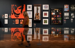 A visitor pases photos and platinum records displayed during a press preview of the exhibition 'Ed Sheeran: Made in Suffolk' in Ipswich, east England on August 19, 2019. - Ipswich, in eastern England has historically prided itself on farming and football, but is now celebrating the stellar pop career of its most famous son, Ed Sheeran. The global hit machine's journey to stardom began in the nearby town of Framlingham, where he played his first gig in front of around 30 people. (Photo by Daniel LEAL-OLIVAS / AFP)
