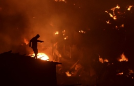 A Bangladeshi man tries to extinguish a fire as a fire blazes in a slum in Dhaka on August 16, 2019. At least 1,000 shanties were gutted as the devastating fire that broke out at Chalantika slum in Dhaka's Mirpur. MUNIR UZ ZAMAN / AFP